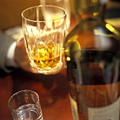 A Hand Holding a Glass of Whiskey in a Bar Setting
