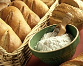 Loaves of Bread in Basket with a Bowl of Flour and Scoop in the Bowl
