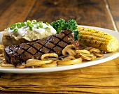 Barbecued beef steak with baked potato and corncob