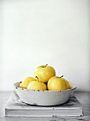 A Bowl of Golden Delicious Apples on a Book