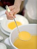 Hand schöpft Butternusskürbis-Suppe aus einem Suppentopf