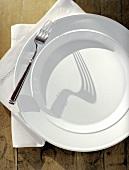 Weisser Teller mit Gabel und Serviette