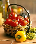 Fresh tomatoes in wicker basket, peppers, green tagliatelle