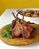 Fried lamb cutlets on wooden plate; stuffed tomatoes