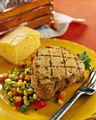 A grilled pork steak with vegetables and bread