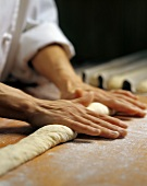 Baker rolling out baguette dough