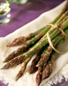 Fresh green asparagus spears on a white napkin