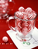 Red and white peppermint sweets in a glass mug