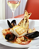 Cod fillet with shrimps and mussels, glass of white wine