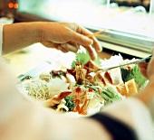 A chef preparing a mixed sushi platter
