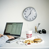 Fast food in the office: hamburger with chips and Cola