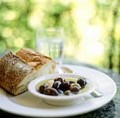 Marinated olives and white bread on table in open air