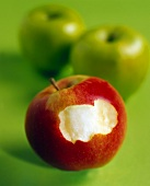 Red apple, a bite taken, in front of two green apples