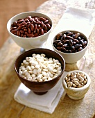 Four types of dried beans in ceramic bowls