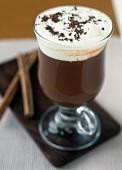 Hot chocolate with cream in glass; cinnamon sticks