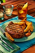 Barbecued ribeye steak with baked potato wedges