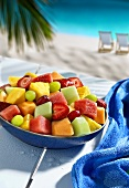 Bowl of fruit salad on table by sea