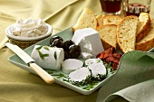 Platter with fresh goat's cheese, slices of bread, olives etc.