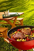 Steaks and vegetables on a barbecue in garden