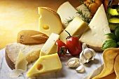 Cheese still life with garlic and tomatoes on marble slab