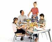 Amerikanische Familie im Stil der 50er Jahre beim Frühstück
