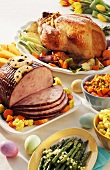 A Baked Ham and Roast Turkey for Easter with Asparagus and Colorful Easter Eggs