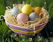 Colorful Easter Basket with Eggs in the Grass