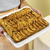 Woman serving tray of freshly baked apple cake