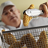 Chef taking chicken nugget out of frying basket