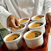 A Chef Placing Oregano Garnish on Bowls of Tomato Soup