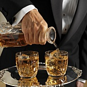 Waiter pouring whisky from carafe into glasses on tray