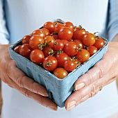 Hands Holding a Container of Grape Tomatoes