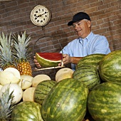 A Man Weighing a Watermelon at a Market Stand