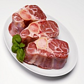 Three Raw Chops for Osso Bucco with Basil on White