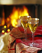 Two Glasses of White Wine Next to a Fireplace