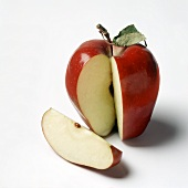 A Red Delicious apple with leaf, a piece cut out