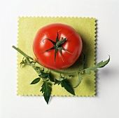 A Red Tomato on a Yellow Cloth with Leaves