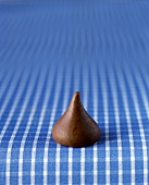 A Single Unwrapped Hershey Kiss on Blue Fabric