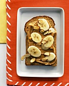 A Slice of Whole Wheat Bread with Peanut Butter, Bananas and Almonds