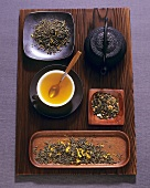 Cup of green tea, teapot and various types of tea leaves