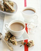 Two cups of coffee with cranberry & pistachio biscotti