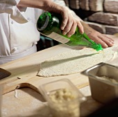 Chef Pouring Oil From Bottle onto Rolled Pizza Dough