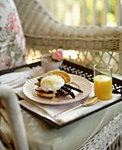 Breakfast Tray with Eggs Benedict on a White Wicker Chair