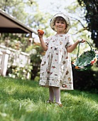 A Girl in a Dress with a Colored Egg and a Basket