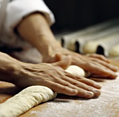 Hands rolling out bread dough