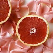 A Pink Grapefruit Half on Pink Rose Petals