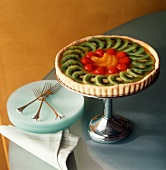 Fruit tart with kiwis, strawberries & oranges on cake stand