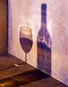 Shadow of wine glass and wine bottle on a wall