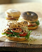 Three bagel sandwiches on wooden table