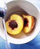 Nectarine Halves in a Bowl with a Spoon